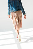 Woman in beige skirt and denim jacket. Rear view, low angle shot of woman in beige skirt and denim jacket walking in white studio Royalty Free Stock Photography