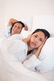 Woman being annoyed by snoring boyfriend Stock Image