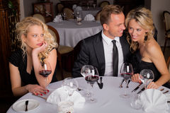 Woman being bored while having dinner with couple. Who are in love Royalty Free Stock Photo