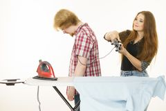 Woman controling man to do ironing. Woman being bossy having fun while steering men using gaming pad. Female controling her boyfriend to do ironing. Household Royalty Free Stock Photo