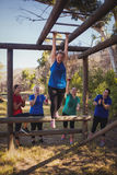 Woman being cheered bye her teammates to climb monkey bars during obstacle course training. In the boot camp Royalty Free Stock Photography