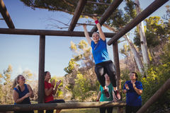 Woman being cheered bye her teammates to climb monkey bars during obstacle course training. In the boot camp Royalty Free Stock Images