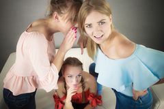 Woman being gossiped by two. Woman being gossiped bullied by two female friends. Friendship difficulties, rivaly and envy problems Royalty Free Stock Photos