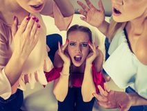 Woman being gossiped by two. Woman being gossiped bullied by two female friends. Friendship difficulties, rivaly and envy problems Stock Image