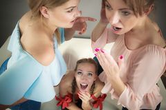 Woman being gossiped by two. Woman being gossiped bullied by two female friends. Friendship difficulties, rivaly and envy problems Stock Photo