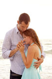 Woman being held close by her man. A woman being held close by her man, they are holding hands and they look like they are having a private with ocean waves in Stock Photo