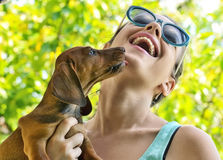 Woman being licked by a dog that she is holding. Stock Photography