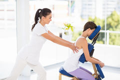 Woman being massaged on chair by masseuse. At spa Royalty Free Stock Image