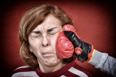 Woman being punched in her face. Woman being punched with red boxing glove in her face. Computer added dust, scratches, grain and vignette Royalty Free Stock Photos