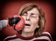 Woman being punched in her face. Woman being punched with red boxing glove in her face. Computer added dust, scratches, grain and vignette Royalty Free Stock Photo