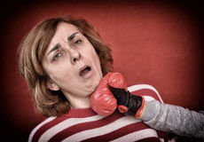 Woman being punched in her face. Woman being punched with red boxing glove in her face. Computer added dust, scratches, grain and vignette Royalty Free Stock Image