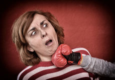 Woman being punched in her face. Woman being punched with red boxing glove in her face. Computer added dust, scratches, grain and vignette Stock Photo