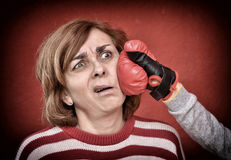 Woman being punched in her face. Woman being punched with red boxing glove in her face. Computer added dust, scratches, grain and vignette Royalty Free Stock Images