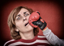 Woman being punched in her face. Woman being punched with red boxing glove in her face. Computer added dust, scratches, grain and vignette Stock Image