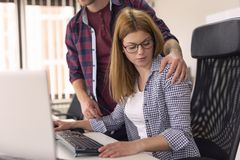 Woman being sexually harassed at work. Businessman sexually harassing female colleague during working hours at a workplace royalty free stock photos