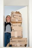 Woman being shocked by Amazon.com delivery. OSTFILDERN-SCHARNHAUSEN, GERMANY - MAY 18, 2014: A woman is horrified by a large stack of parcels by Amazon.com in royalty free stock images