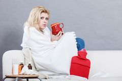 Woman being sick having flu lying on sofa Stock Photos