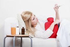Woman being sick having flu lying on sofa Royalty Free Stock Photos