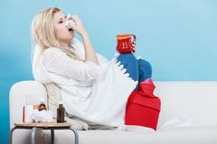 Woman being sick having flu lying on sofa Stock Photos