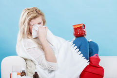 Woman being sick having flu lying on sofa Royalty Free Stock Image