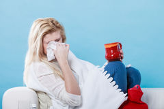 Woman being sick having flu lying on sofa Stock Image