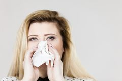 Woman being sick having flu sneeze into tissue Stock Photography