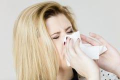 Woman being sick having flu sneeze into tissue Stock Photos