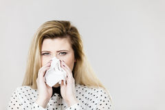 Woman being sick having flu sneeze into tissue Royalty Free Stock Photos
