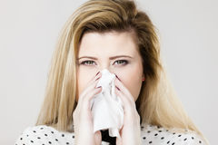 Woman being sick having flu sneeze into tissue Royalty Free Stock Photography