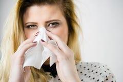 Woman being sick having flu sneeze into tissue Stock Photo
