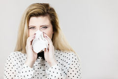 Woman being sick having flu sneeze into tissue Stock Image