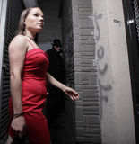 Woman being stalked. Woman in a red dress being followed Stock Image