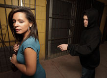 Woman being stalked. Man stalking a woman and reaching to grab her purse royalty free stock photography
