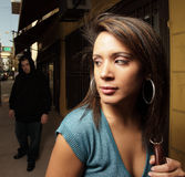 Woman being stalked by a thug. Young woman glancing over her shoulder at a stalker following her in the streets Royalty Free Stock Image