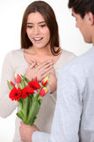 Woman being surprised with bunch of flowers Stock Images