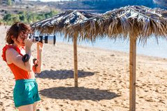 Woman taking pictures during holiday in Greece. Woman being on vacations taking pictures druing traveling. Female photographer photographing nature in Greece royalty free stock image