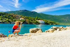 Woman taking pictures during holiday in Greece. Woman being on vacations taking pictures druing traveling. Female photographer photographing pier in Greece stock image