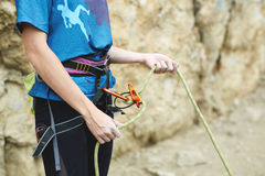 Woman belaying other climber through a belay device. Stock Photo
