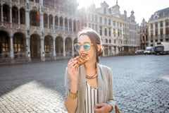 Woman with belgian waffle outdoors. Young woman walking with waffle a traditional belgian pastry food in the center of Brussels city during the morning Stock Photos