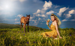 Woman belly dancer relaxing on grass field against blue sky with white clouds Stock Photos