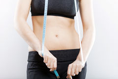 Woman belly and measuring tape, weight loss concept Royalty Free Stock Photo
