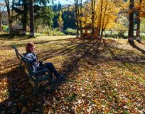 Woman on bench in autumn Carpathian mountain sunny park on river. Woman on bench and open air gazebo in autumn Carpathian mountain sunny park on White Tysa river Royalty Free Stock Image