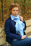 Woman on bench in autumn park Stock Photos