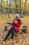 Woman on bench in autumn park. Royalty Free Stock Images