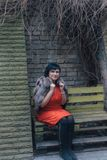 Woman on bench in city. Brunette woman is sitting on a bench on an autumn day in the city Stock Images