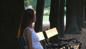 Woman on a bench in the park at sunset. Young woman sitting on a bench in the park and looks toward the setting sun, which with its rays illuminates a woman and stock video footage