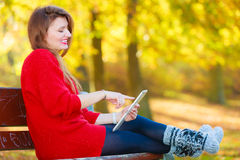 Woman on bench in park with tablet. Stock Images