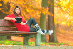 Woman on bench in park with tablet. Royalty Free Stock Images