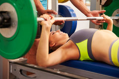 Woman bench pressing weights with assistance of trainer stock photos