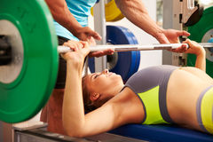 Woman bench pressing weights with assistance of trainer Stock Image